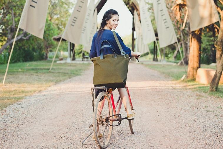 【写真】SALASUSUのカバンを斜めがけして自転車にまたがる女性