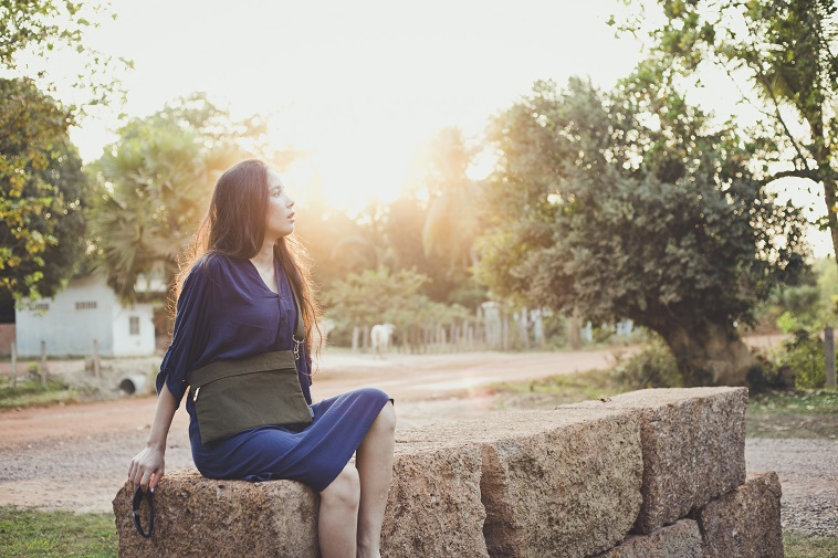 【写真】バッグを肩にかけ、屋外で石畳に座る女性