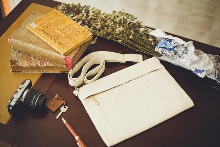 【写真】机の上に本やカメラと一緒に並べられたSALASUSUのバッグ