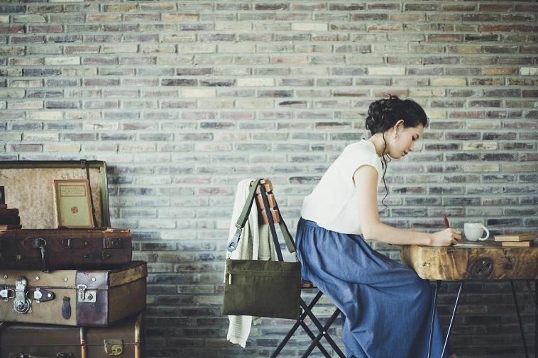 【写真】椅子に座り机でメモをとる女性。椅子にはバッグがかけられている