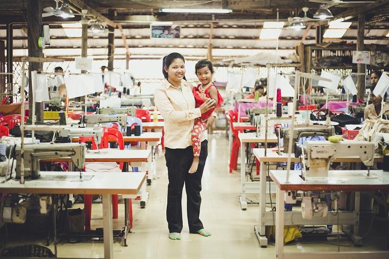 【写真】工房内で子どもを抱っこしながら微笑む女性