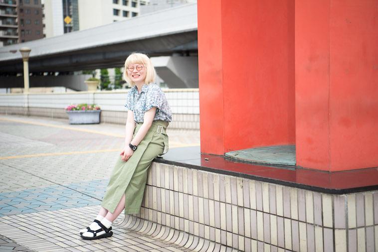 【写真】駅前のいすに腰掛けながら笑顔でうつるかんばらゆかさん