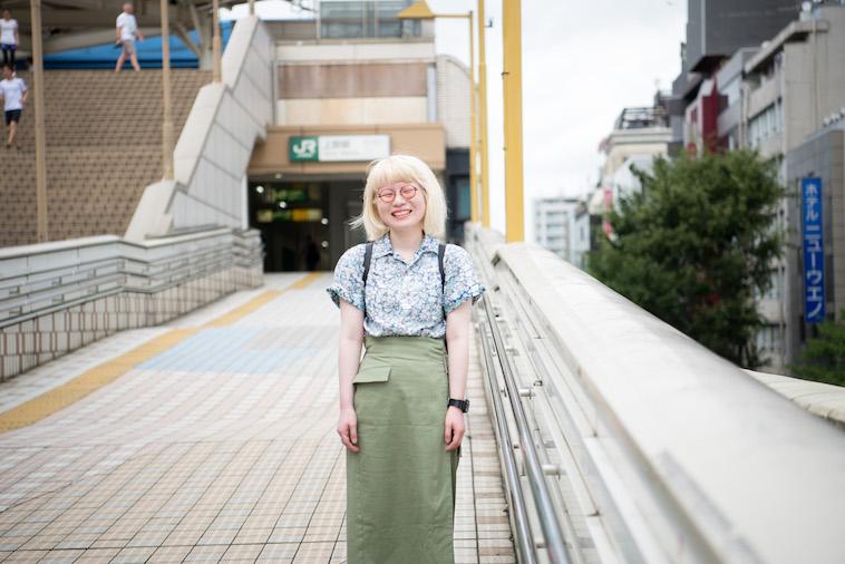 【写真】駅の前で、笑顔で立っているかんばらゆかさん