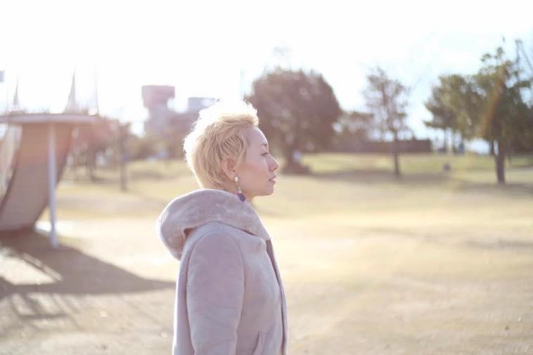 【写真】金髪のたかはしえまさん。光が差す公園の中で、まっすぐどこかをみつめている。