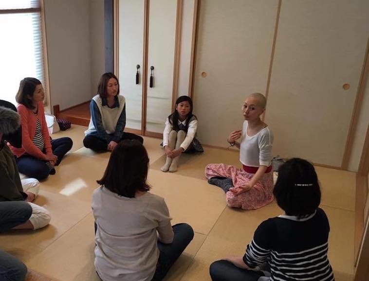 【写真】和室の部屋に7人ばかり集まっている。その中で乳がんについて話すたかはしさん。参加者たちは真剣に話を聞いている。