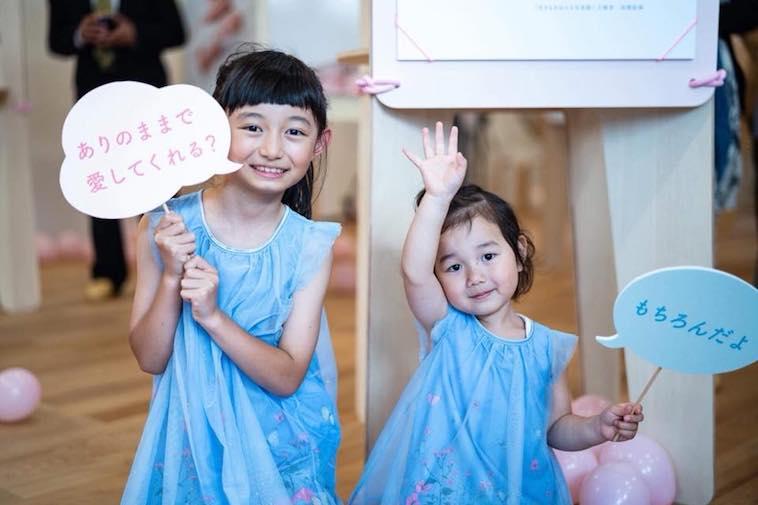 【写真】写真展に来たふたりの笑顔の子供たちがうつっている。その手には、「ありのままで愛してくれる?」「もちろんだよ」と書かれたプラカードを持っている。