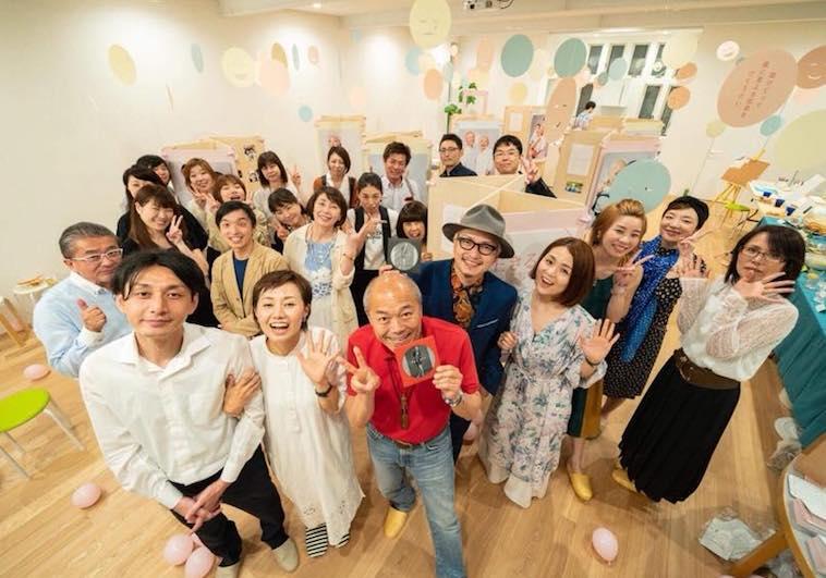 【写真】写真展に関わったたかはしさんとスタッフの集合写真。みんなポーズをとったり明るい笑顔で楽しそうだ。