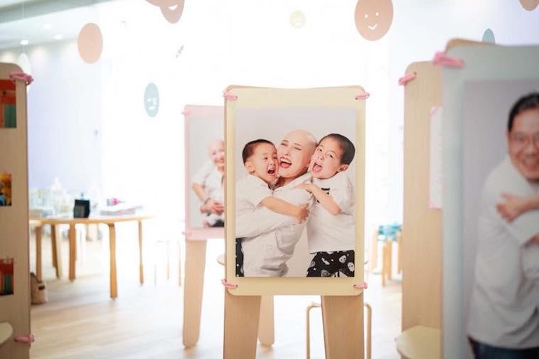 【写真】写真展の様子。中心には、笑顔の2人の子供に抱きつかれているたかはしえまさんの大きい写真が飾られている。