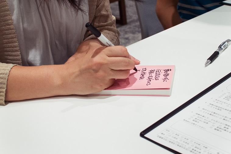 【写真】本の表紙に何かを書き込んでいる参加者