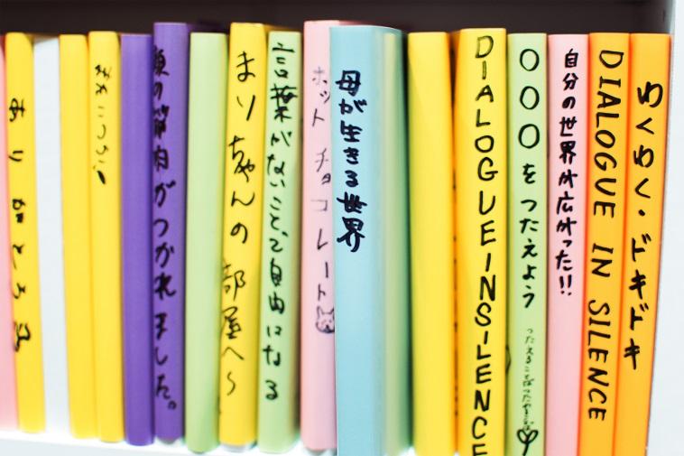 【写真】参加者が書いた本が並んだ本棚。真ん中にはライターのいそださんが書いた本がおかれている。タイトルは「母が生きる世界」