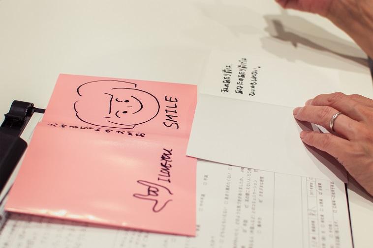 【写真】参加者が書いた本のカバーの写真。えみるちゃんの笑顔と書き、えみるちゃんのイラストとスマイルという文字は大きく描かれていた。