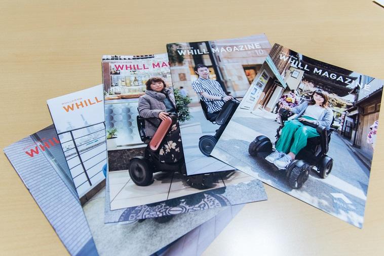 【写真】うぃるの広報誌の「うぃる まがじん」が並んでいる。それぞれ表紙には、うぃるの車椅子にのって笑顔でほほんでいる人々がうつっている。