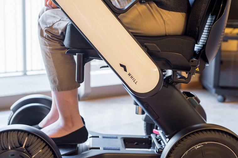 【写真】車椅子に乗っているきどさんの足元。車椅子の側面には「うぃる」と書かれている。