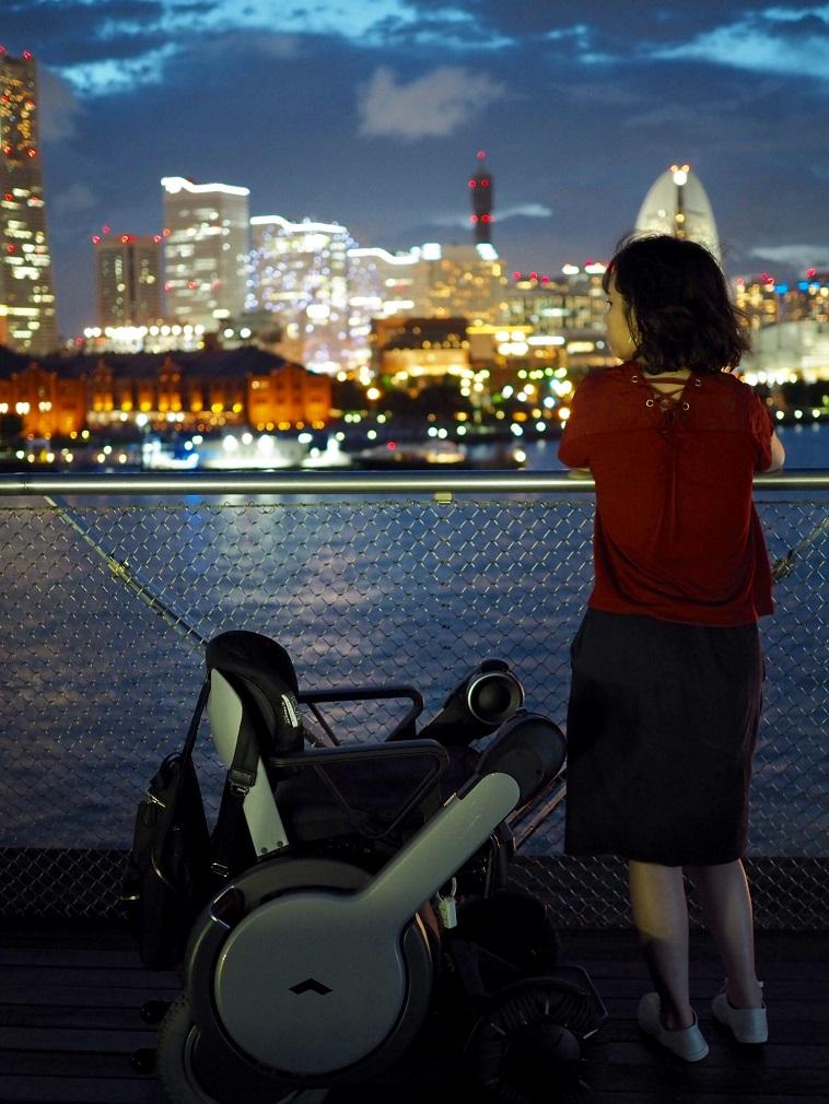 【写真】夜景をみているきどかなえさんの後ろ姿と、車椅子がうつっている。