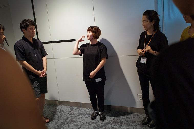 【写真】アテンドを務めるえみるさんが身振り手振りを使用し説明している。参加者たちは真剣に聞いている。