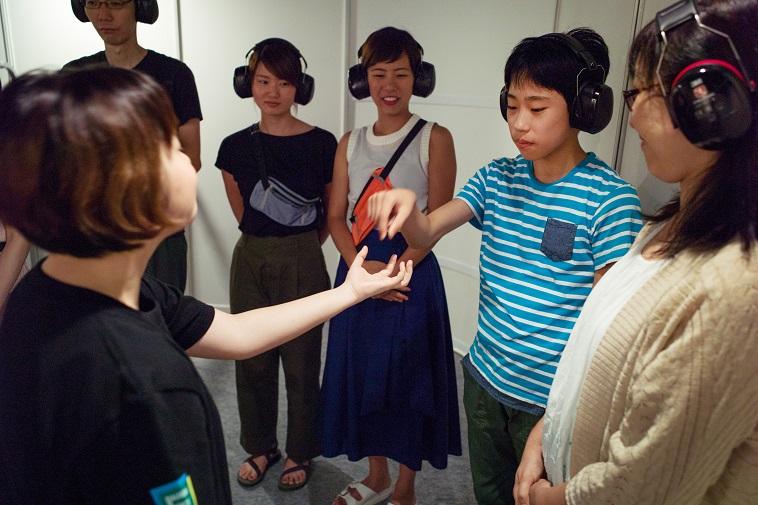 【写真】えみるさんに「声帯」を預けるジェスチャーをする参加者。