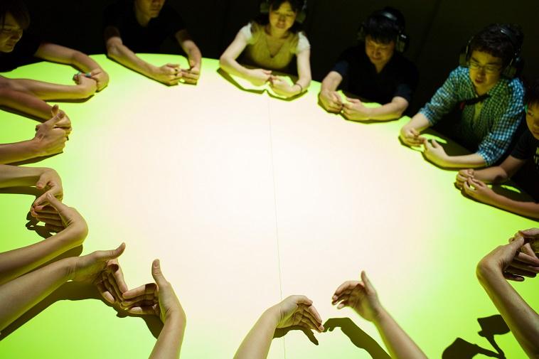 【写真】丸い机を囲み、参加者たちが手遊びをしている。