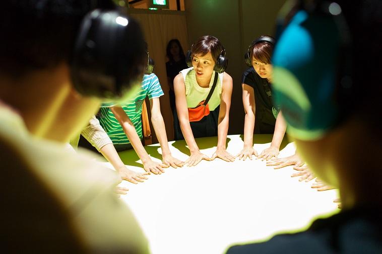 【写真】参加者たちが丸い机に手をおいている。