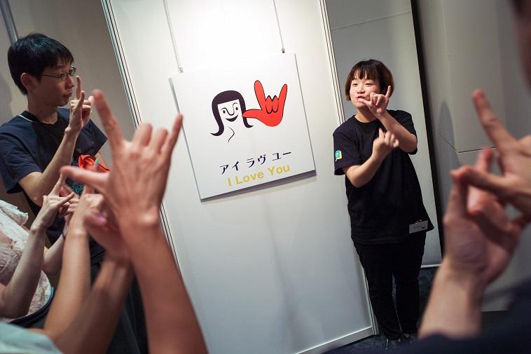 【写真】アイラブユーの手話を実践する参加者たち。中指と薬指のみを折りたたみ、他の指は広げている。