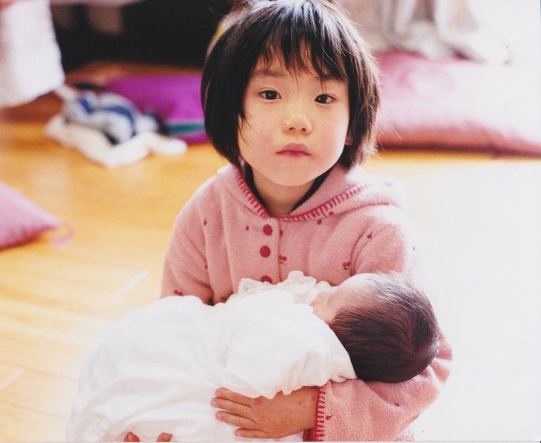 【写真】幼少期のきどかなえさん。赤ちゃんを抱っこしている。