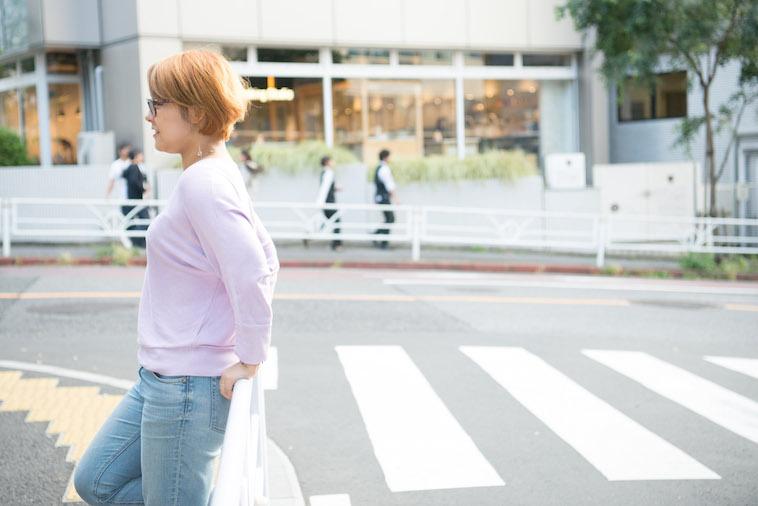 【写真】街頭のガードレールに明るい表情で腰掛けるますぶちみなこさん