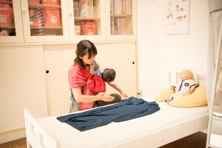 【写真】赤ちゃんを抱いて服を選ぶのぐちゆりさん