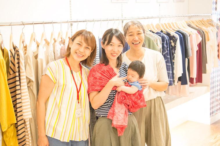 【写真】様々な服の前で笑顔で立っているかつまさみきさんと赤ちゃんを抱いているのぐちゆりさん