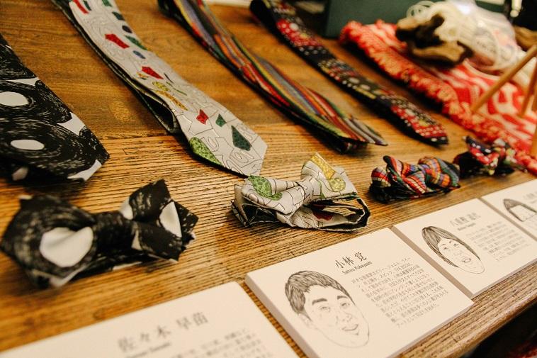【写真】むくの商品の蝶ネクタイがいくつか並んでいる。その下には制作したアーティストの紹介文がおかれている。