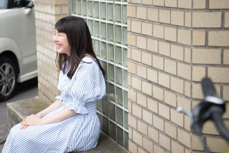 【写真】外の椅子にすわり、笑顔のやまねゆうかさん