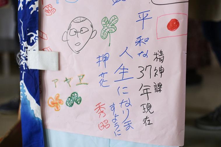 【写真】紙に人の顔や葉っぱのイラストと、「平和な人生になりますように」「押花」「秀昭」「精神課37年現在」などと書かれている