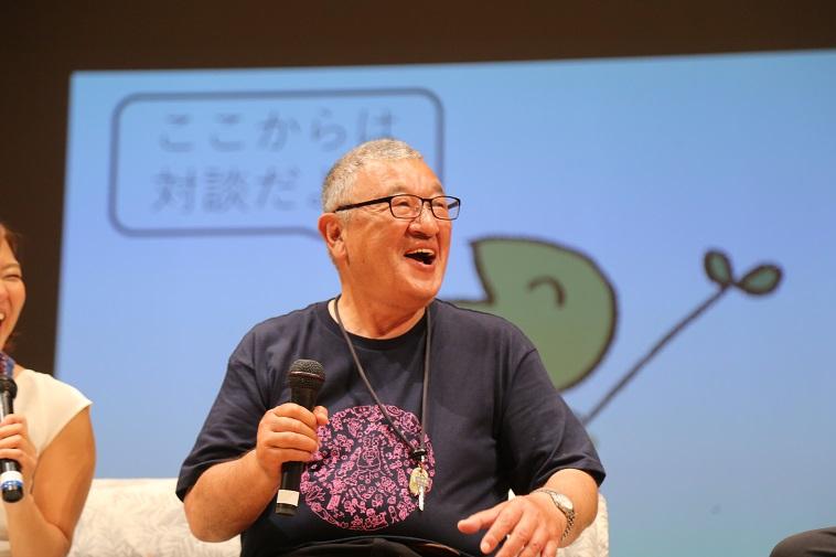 【写真】実行委員のはやさかきよしさんが笑顔でマイクを持っている
