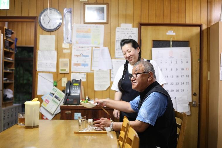 【写真】べてるの家で夕食を食べるはやさかきよしさん。べてるスタッフが横で微笑んでいて、温かい雰囲気