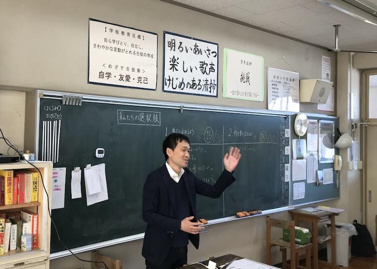 【写真】出張授業をしているたにやまさん。黒板の前で身振り手振りを交えて楽しそうな様子で説明している。