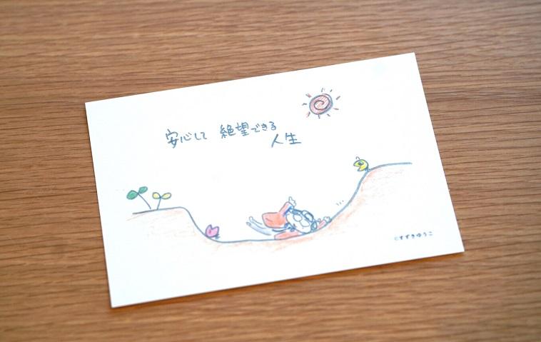 【写真】「安心して絶望できる人生」のもじと、むかいやちいくよしさんをモデルにしたほっこりするイラストが書かれたポストカード