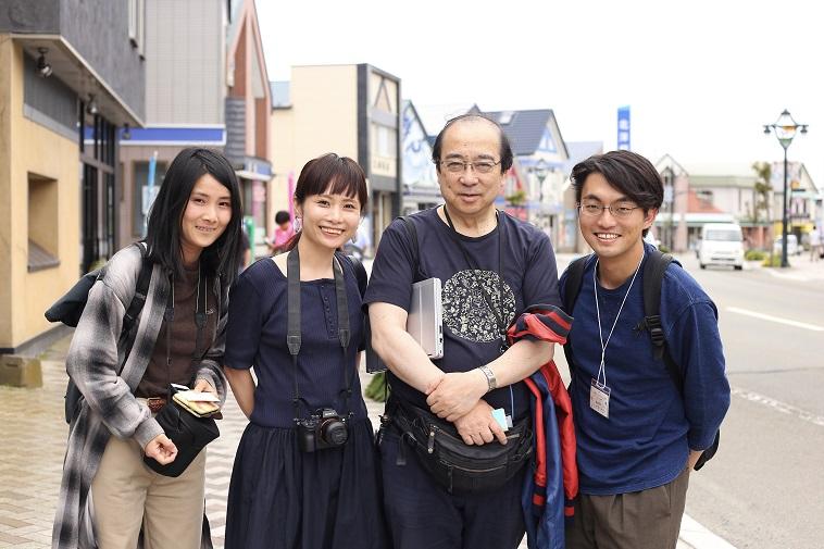 【写真】むかいやちいくよしさんと取材メンバーが浦河の街をバックに笑顔を向けている