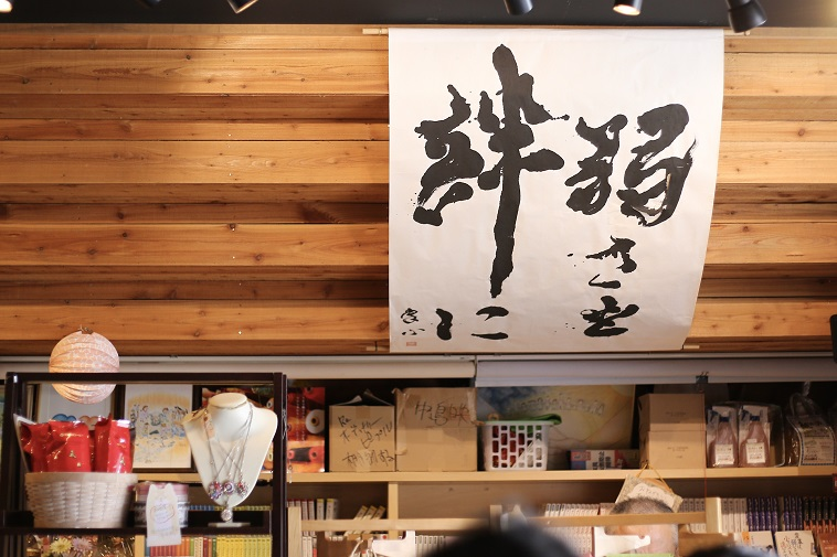【写真】温かみのある木の壁に「弱さを絆に」と書いた書が飾ってある