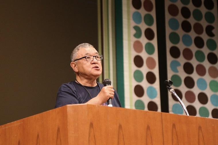 【写真】ステージの上でマイク片手に話をするべてるまつり実行委員長のはやさかきよしさん。真剣な表情をしている