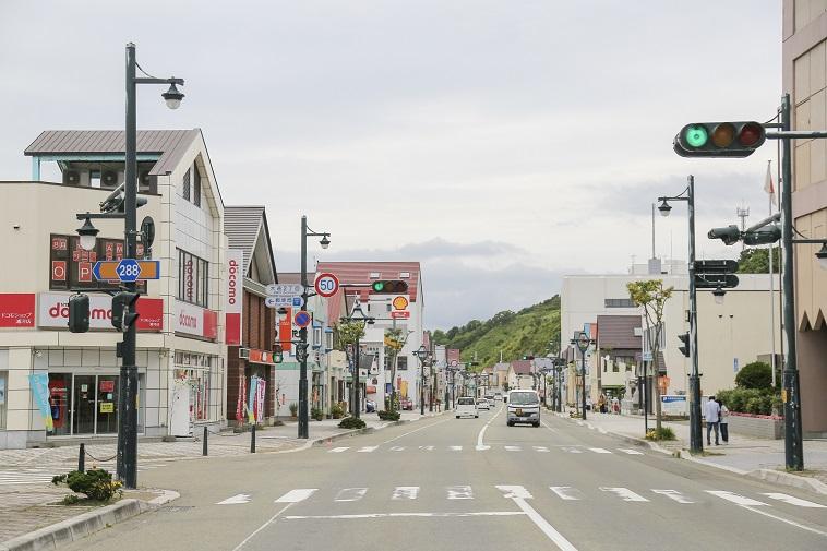【写真】浦河の交差点。広い道路に家々や店が並ぶ。車の通りは多くない