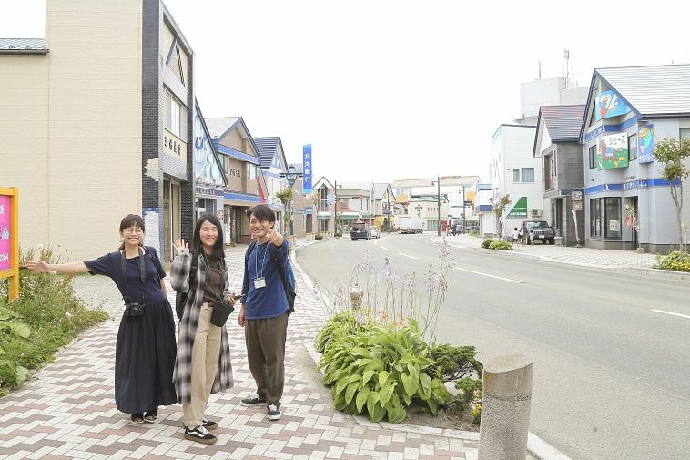 【写真】浦河の街を背景に、soar取材メンバー3人がカメラに向かって笑顔でポーズをとっている