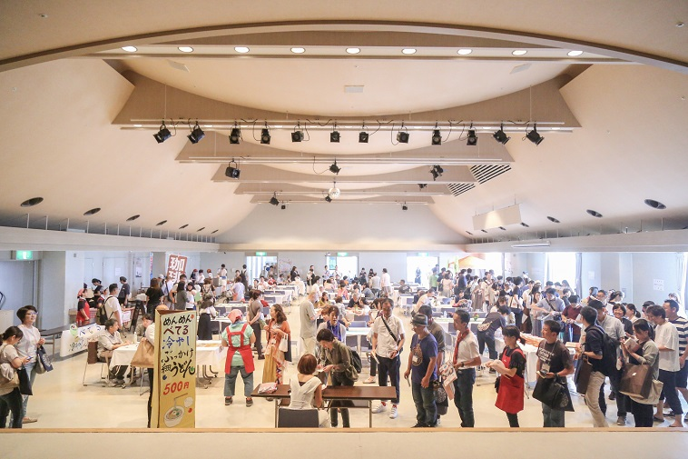 【写真】物販のマルシェブース。「珈琲」「めんめんべてる 冷やしぶっかけうどん」など書かれた看板がある。広い空間にたくさんの人が並んでいる