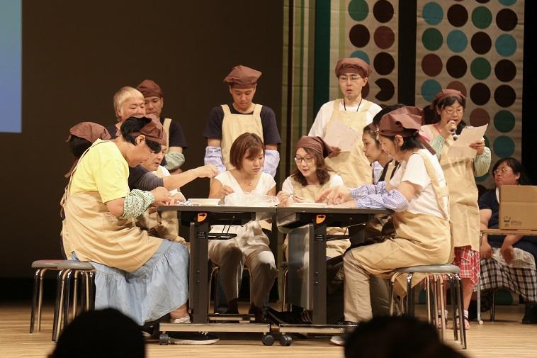 【写真】机を囲んで椅子に座るべてるメンバーたち。三角巾をつけて作業場の様子を再現している
