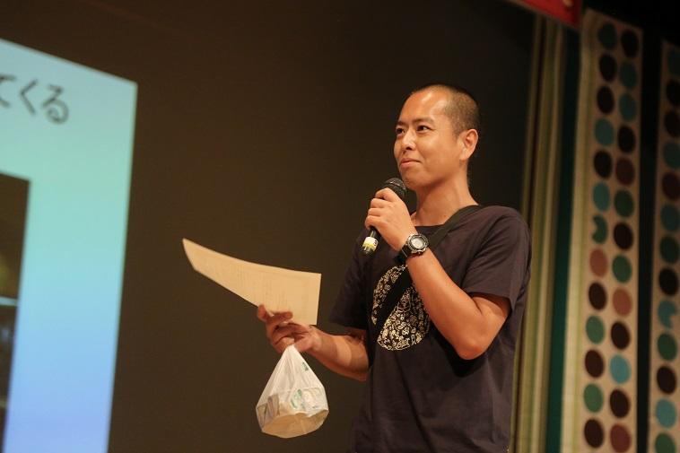 【写真】サトウシンゴさんが賞状を片手にマイクを持って話している