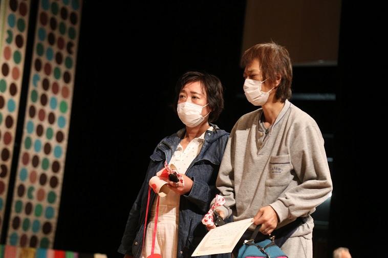 【写真】タカトリヨシアキさんとナカニシアツコさん。二人ともマスクをし、浮かない表情をしている