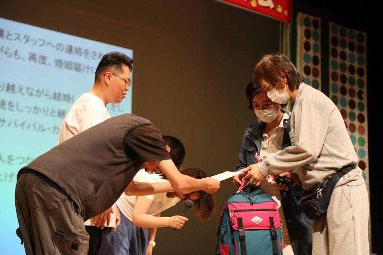 【写真】べてるメンバーから賞状を受け取るタカトリヨシアキさんとナカニシアツコさん
