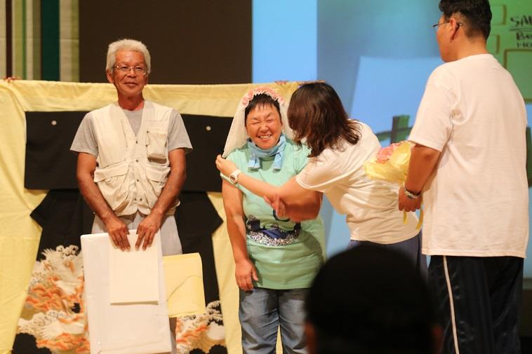 【写真】べてるまつりの様子。ステージの上で女性がベールをつけてもらっている