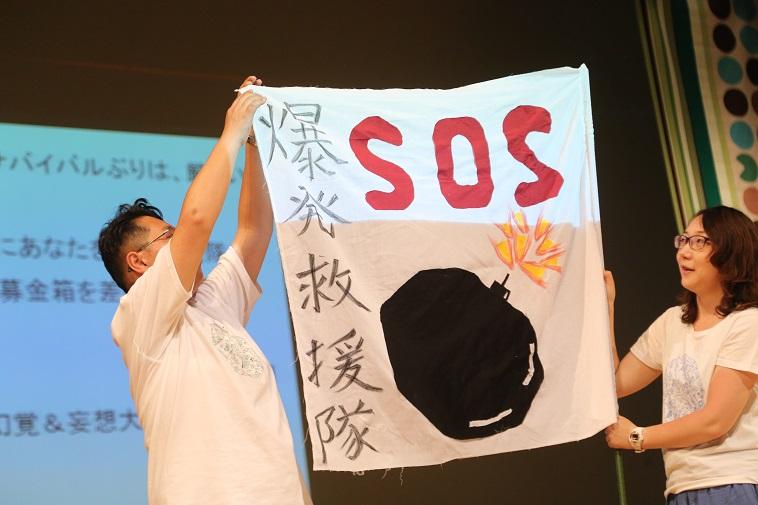 【写真】べてるメンバーが、「爆発救援隊 SOS」の文字と爆弾の絵が描かれた旗を持っている