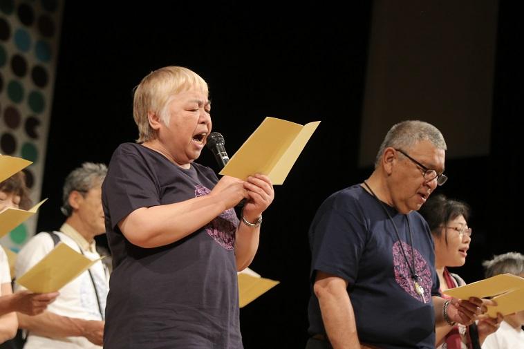【写真】歌詞カードをみながら大きな口を開けて、マイク片手に歌を歌うべてるメンバー