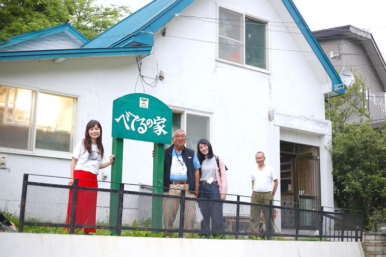 【写真】べてるの家と書かれた看板の前で微笑むはやさかきよしさんと、取材メンバー