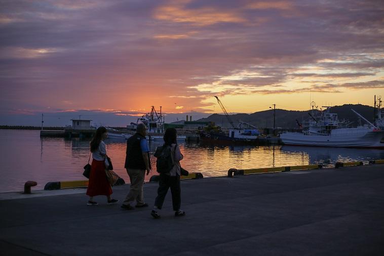 【写真】浦河町の海沿いの道を歩く、はやさかきよしさんとsoar取材チーム。バックには夕日が沈んでいく美しい情景が