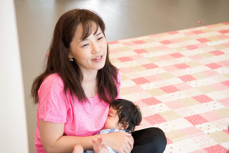 【写真】赤ちゃんを抱えて微笑んでインタビューに答えるりささん